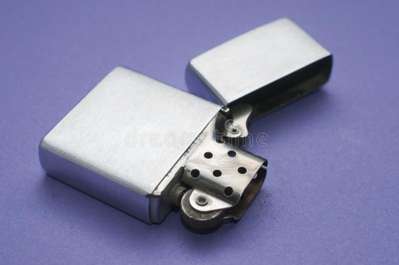 Пустой лихтер металла открытый на пурпурной таблице стоковое изображение