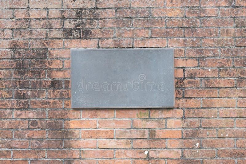 Пустой номерной знак дома утюга на кирпичной стене с выдержанной и запятнанной предпосылкой текстуры стоковые изображения rf