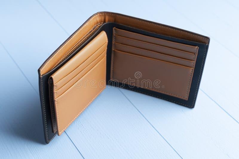 Пустой открытый кожаный кошелек на фоне деревянно-голубой доски стоковая фотография