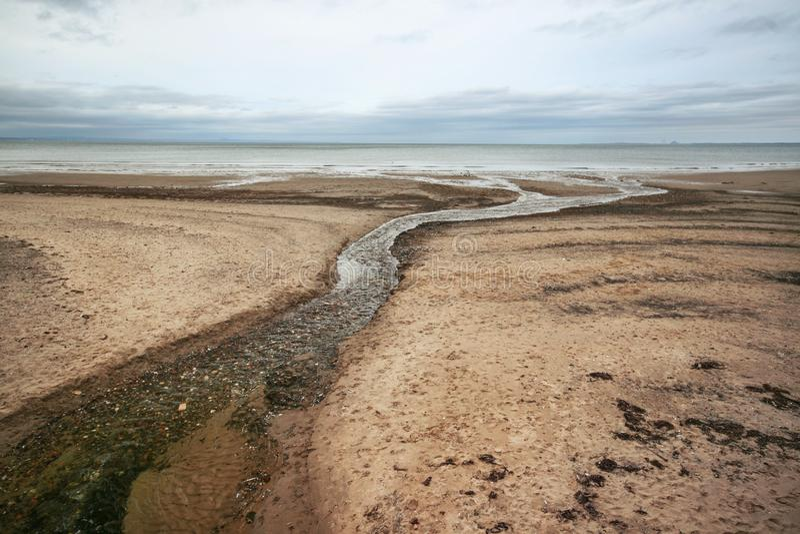 Пустой пляж, при поток воды водя к морю, на день overcast стоковые изображения rf