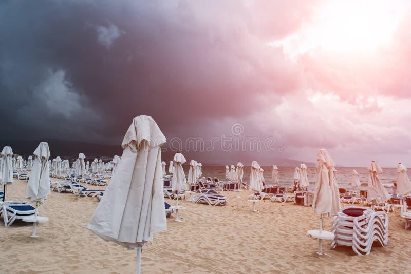 Пустой пляж с креслами для отдыха и зонтиками перед дождем в сезоне лета стоковое фото rf