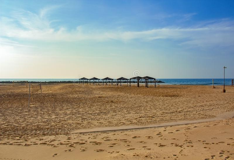 Пустой пляж с сен солнца и сетью волейбола стоковая фотография