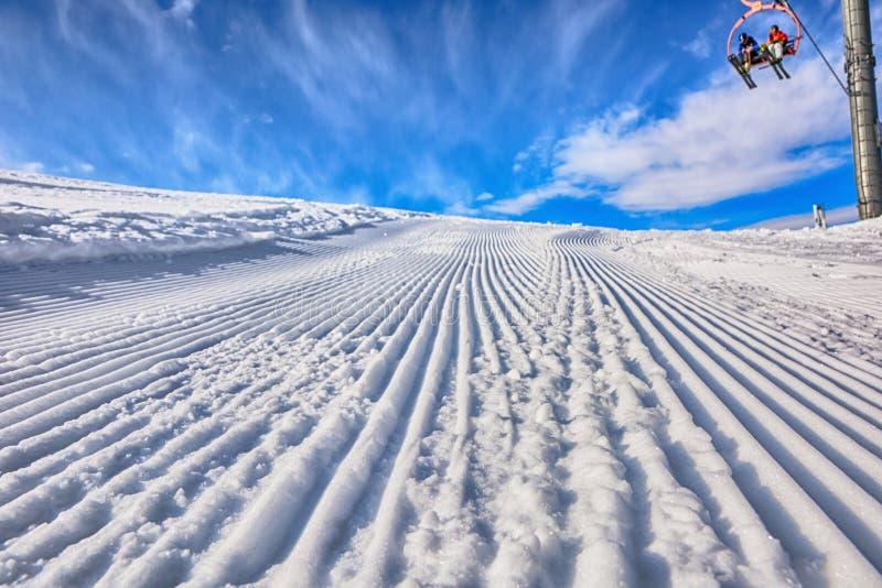 Пустой путь лыжи в лыжном курорте после проходить тележку и людей на стульях лыжи день солнечный стоковое изображение rf