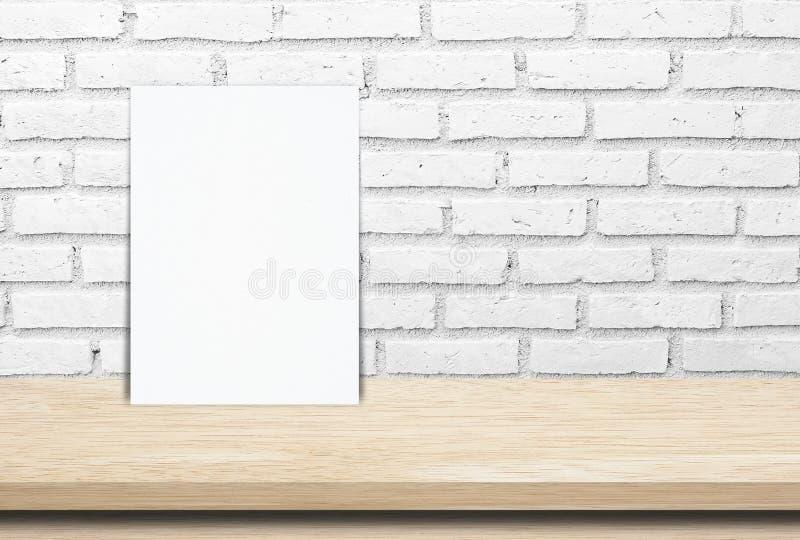 Пустой плакат белой бумаги над деревянной предпосылкой таблицы и кирпичной стены стоковое изображение rf