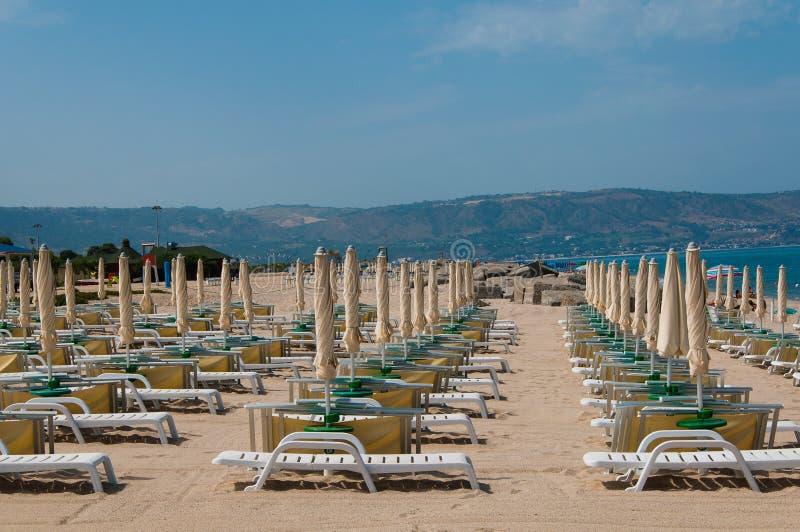 Пустой пляж с креслами для отдыха & зонтиками стоковое изображение