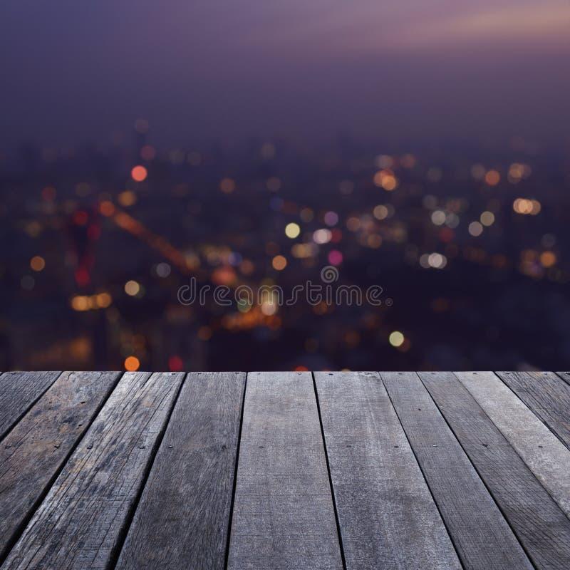 Пустой старый деревянный пол над башней города света нерезкости стоковые изображения rf