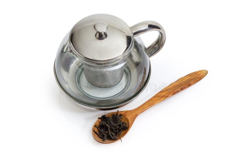 Пустой стеклянный чайник и высушенные листья чая в деревянной ложке стоковое изображение rf