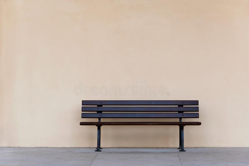 Пустой стул деревянной скамьи против пустой стены стоковое изображение