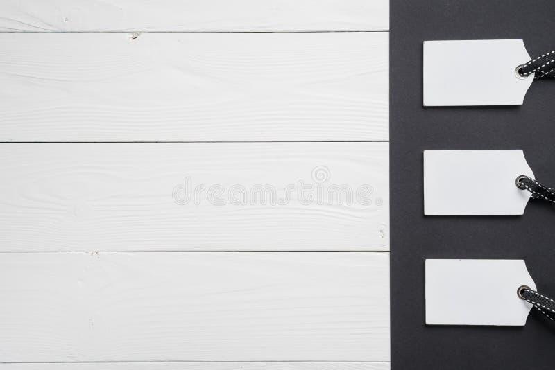 Пустые белые бирки в ряд на белой и черной деревянной предпосылке Взгляд сверху насмешка вверх по образцу Пустой ценник на деревя стоковые фотографии rf