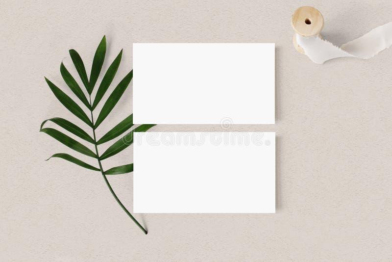 Пустые белые модель-макеты визитных карточек с лентой лист и шелка ладони на текстурированном backgound таблицы Элегантный соврем стоковое изображение rf