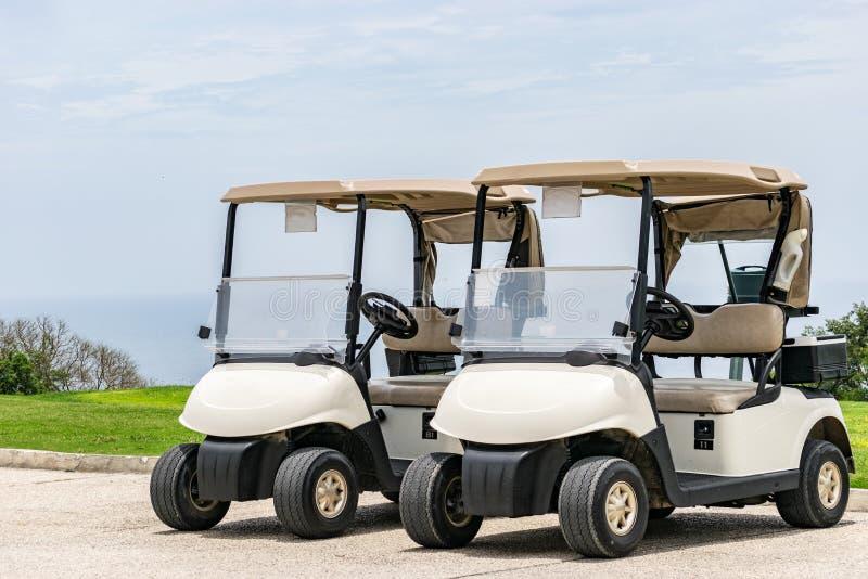 Пустые белые тележки гольфа припарковали сторону - - сторона стоковые фотографии rf