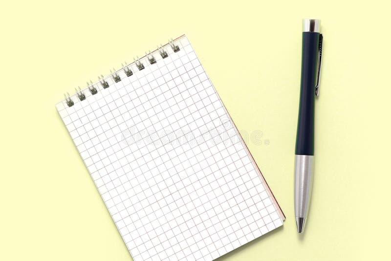 Пустые блокнот и ручка на желтой предпосылке r стоковое изображение rf