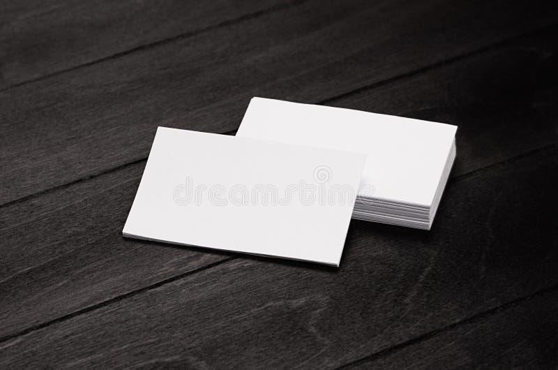 Пустые визитная карточка и стог фирменного стиля на черной стильной деревянной предпосылке с нерезкостью, шаблоном стоковые фото