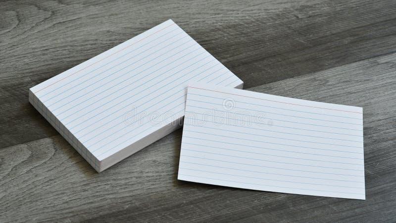 Пустые внезапные карточки примечания индекса на темной серой деревянной предпосылке стоковое фото
