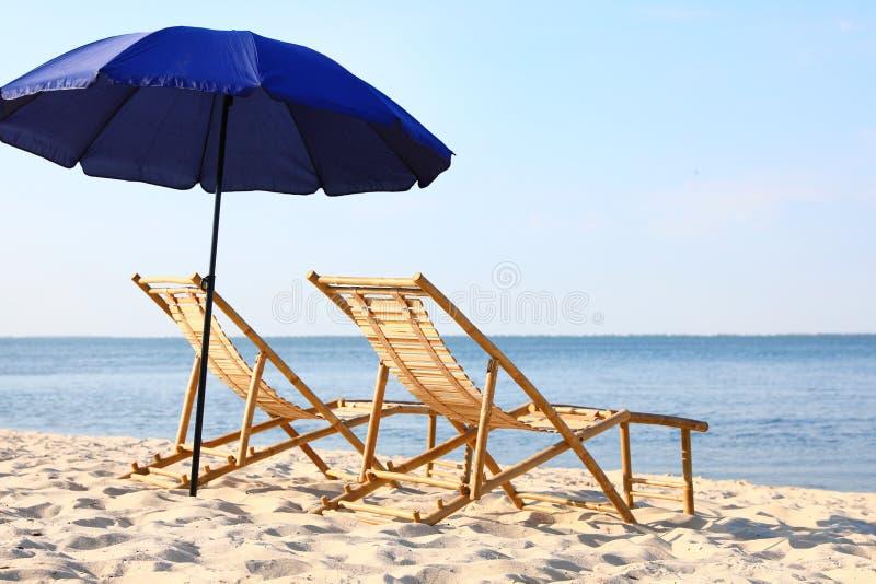 Пустые деревянные sunbeds и зонтик на песочном береге E стоковые изображения