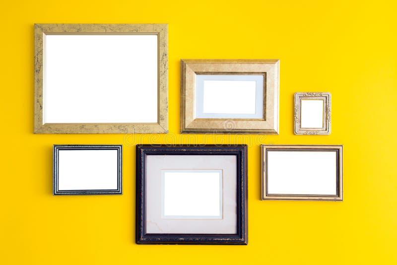 Пустые пустые золотые, деревянные рамки на желтой предпосылке Кнопперс искусства стоковые изображения