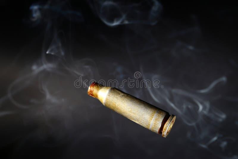 Пустые кожухи раковины пули, на черной предпосылке, курят стоковые фотографии rf