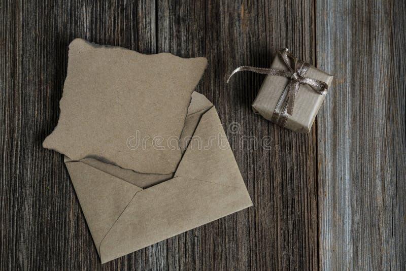 Пустые письмо и подарочная коробка на деревянном столе стоковое изображение rf