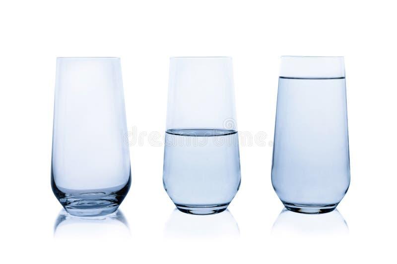 Пустые, половинные и полные стекла воды на белизне стоковая фотография