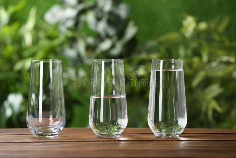 Пустые, половинные и полные стекла воды на деревянном столе стоковое изображение
