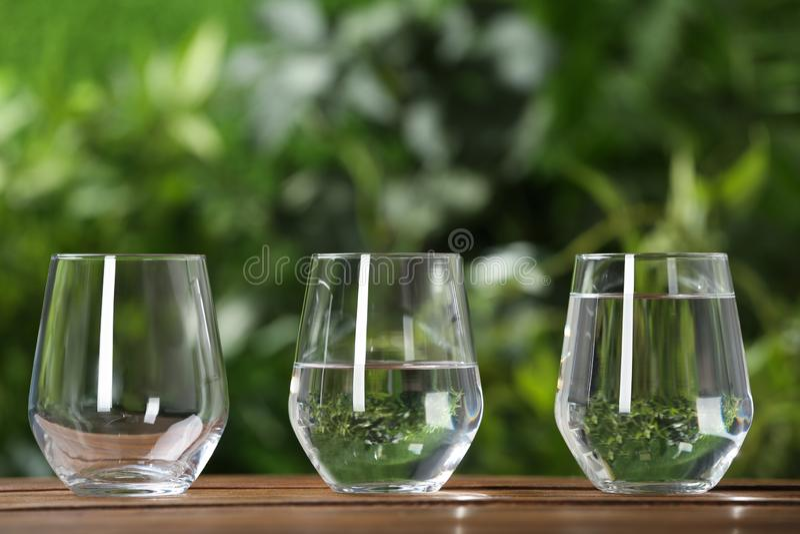 Пустые, половинные и полные стекла воды на деревянном столе стоковая фотография rf