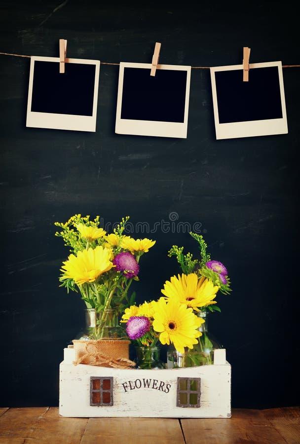 Пустые пустые немедленные фото висят на веревочке над букетом лета цветков на деревянном столе с черной предпосылкой стоковое изображение rf