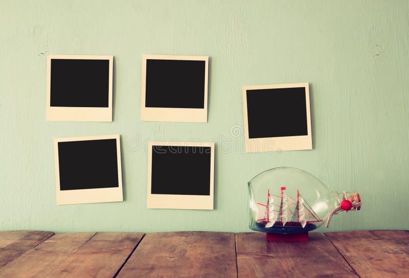 Пустые пустые немедленные фото висят над деревянной текстурированной предпосылкой рядом с декоративной шлюпкой в бутылке ретро фи стоковое фото rf