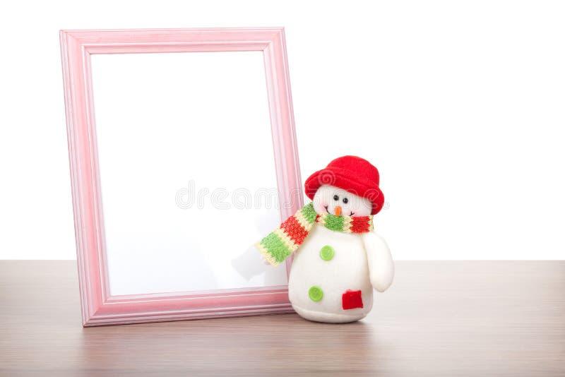 Пустые рамка фото и снеговик рождества на деревянном столе стоковые изображения rf