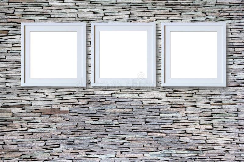 Пустые рамки на каменной стене стоковые изображения