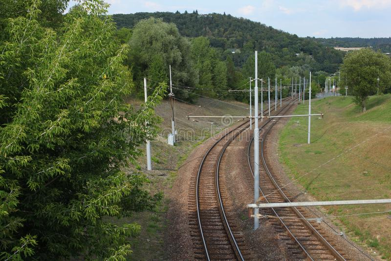 Пустые рельсовые пути трамвайной линии, с зелеными деревьями и травой вокруг BR стоковые изображения