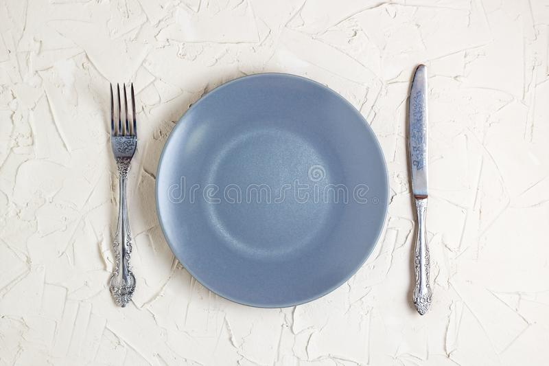 Пустые серые плита, вилка и нож на белой предпосылке Взгляд сверху с космосом текста стоковые изображения rf