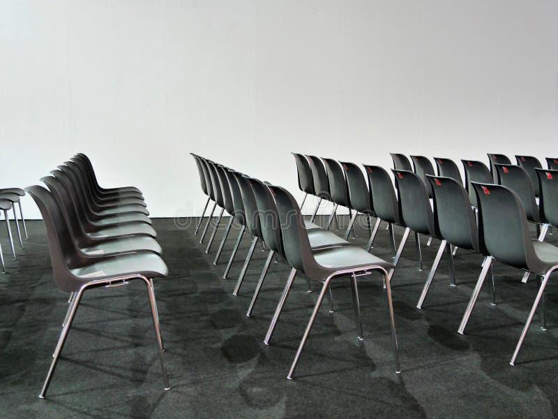 Пустые строки стульев на белой предпосылке стоковое фото
