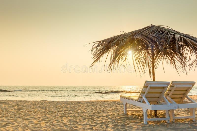 Пустые стулья под покрыванными соломой зонтиками на песчаном пляже стоковое изображение