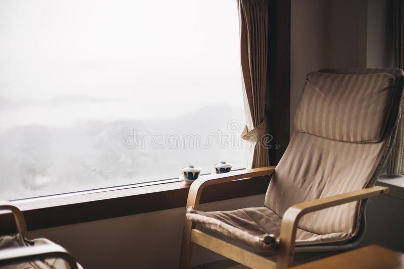 Пустые стулья и чашка чая на окне на дождливый день стоковое фото