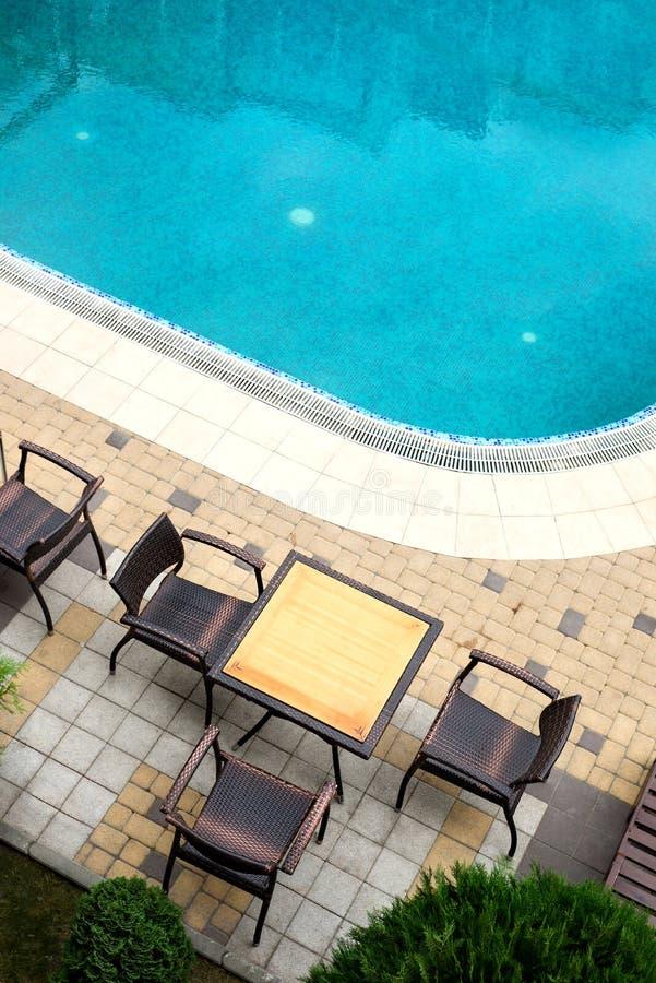 Пустые таблица и стулья ротанга рядом с бассейном Каникулы и tra стоковое изображение rf