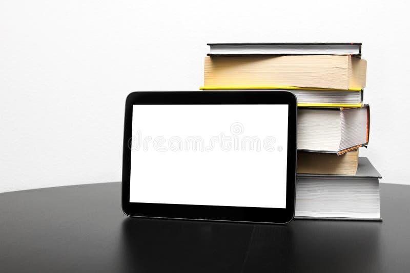 Пустые цифровые таблетка и стог книг стоковые фотографии rf