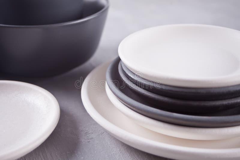 Пустые черно-белые плиты над серой таблицей стоковые изображения rf