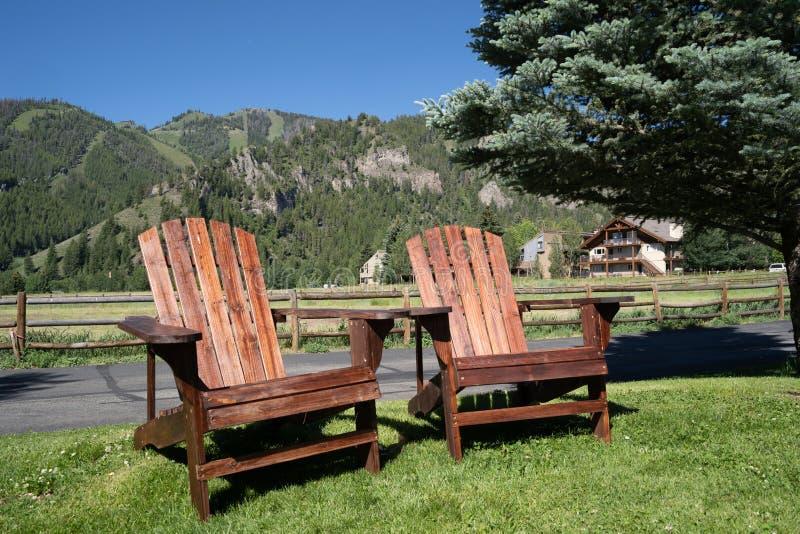 2 пустых деревянных стуль adirondack сидят на траве, обозревая горы Sawtooth Айдахо Принятый в Ketchum, ID стоковые фото