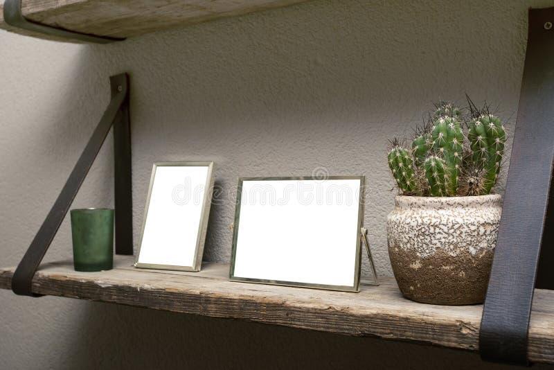 2 пустых картинные рамки и украшения кактуса на деревянной полке, промышленном ретро дизайне интерьера стоковое фото