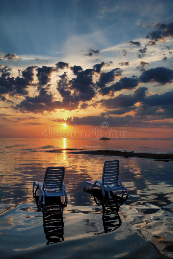 2 пустых шезлонга с тенью в воде пляж на солнцах стоковая фотография