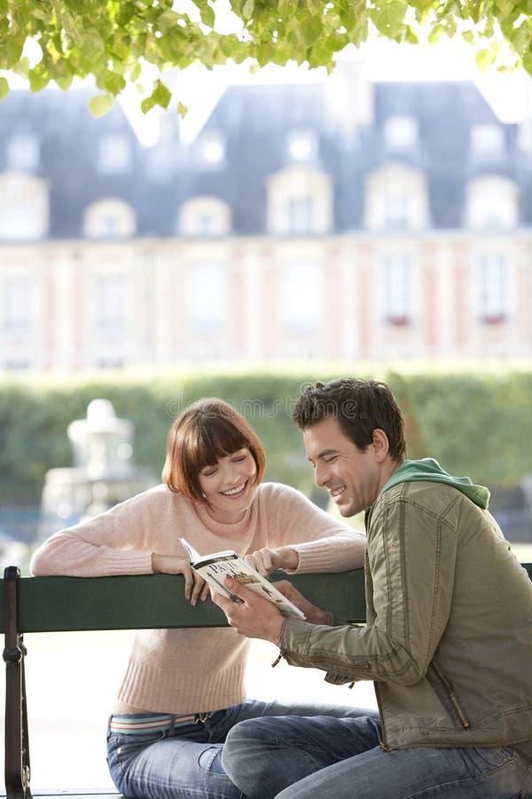 Путеводитель чтения пар на скамейке в парке стоковые изображения