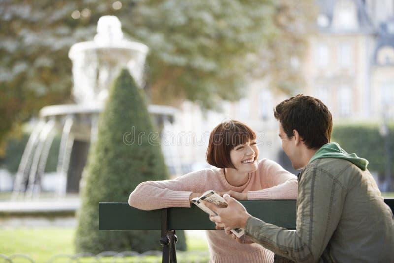 Путеводитель чтения пар на скамейке в парке стоковое изображение rf