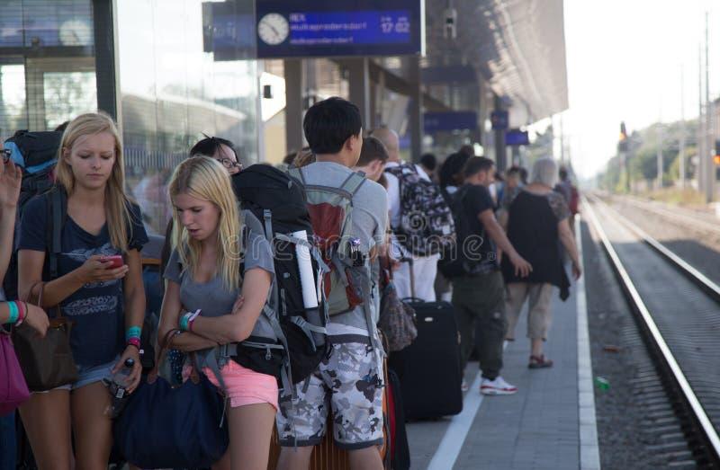 Путешественники ждать поезд в переполненной станции стоковая фотография