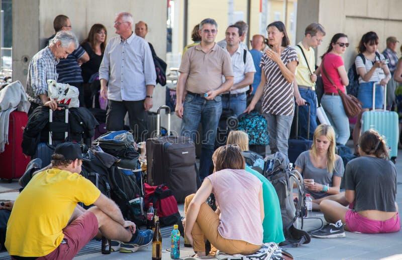 Путешественники ждать поезд в переполненной станции стоковое изображение