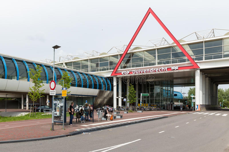 Путешественники ждут на автобусной остановке около голландского железнодорожного вокзала стоковое фото