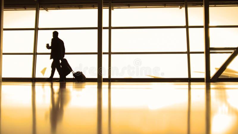 Путешественники - командир экипажа самолета с кофе, который нужно пойти пойти в авиапорт перед окном, силуэтом, теплым стоковые изображения