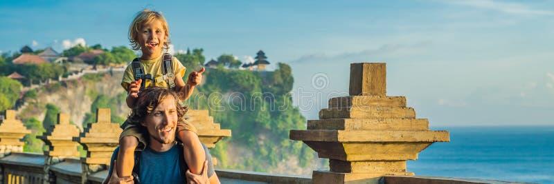 Путешественники папы и сына в виске Pura Luhur Uluwatu, Бали, Индонезии Изумительный ландшафт - скала с голубым небом и морем стоковое изображение