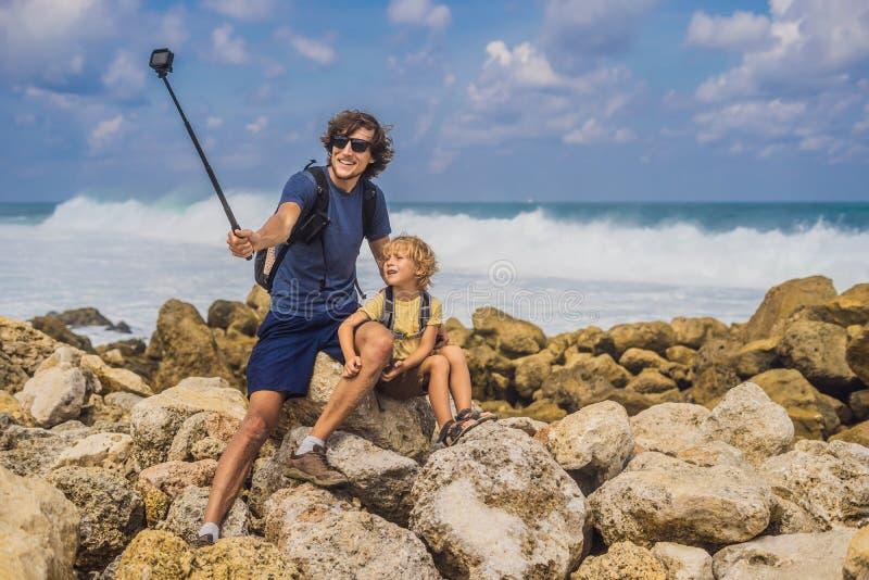 Путешественники папы и сына на изумлять пляж Melasti с водой бирюзы, островом Индонезией Бали Путешествовать с концепцией детей стоковое фото