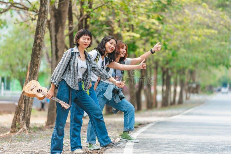 Путешественники пробуют остановить автомобиль Автостопщики друзей путешествуя день лета солнечный Путешественники друзей компании стоковое фото