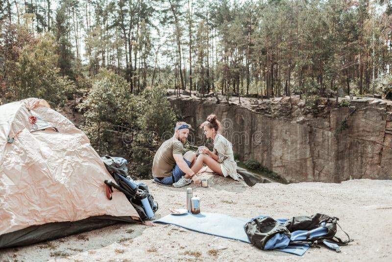 Путешественники сидя на краю скалы около озера слушая к музыке и выпивая чаю стоковые изображения rf